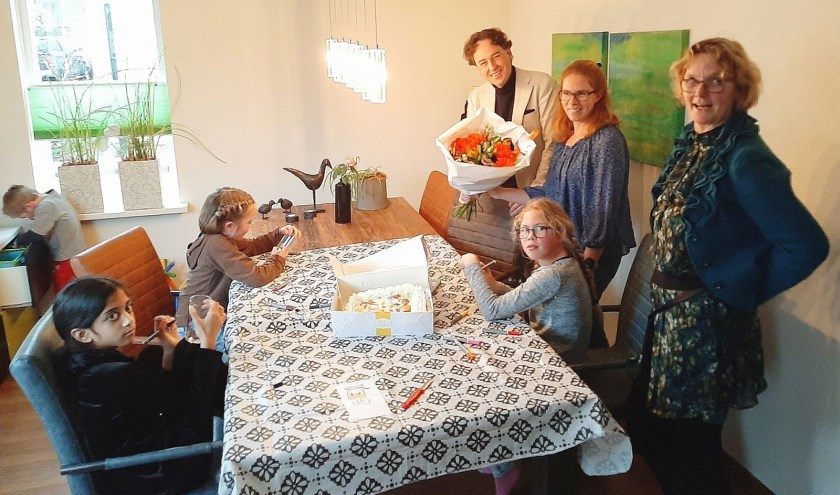 Een feestje bij de vijftigste koppeling van Buurtgezinnen: bloemen voor moeder  (midden) en taart voor de kinderen. (Foto: Rinus Verweij)