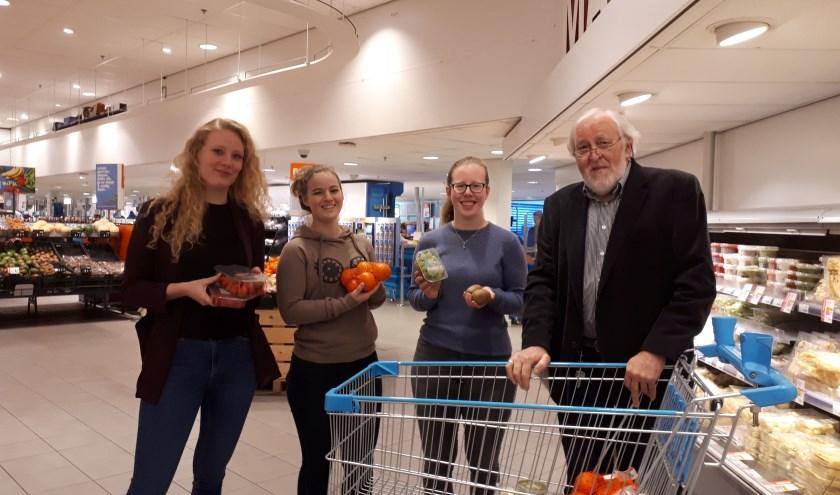 Mylene Eenhoorn, Louise Disselen en Merle te Focht geven AH-klant Jaap van der Laan uitleg over gezonde voeding.