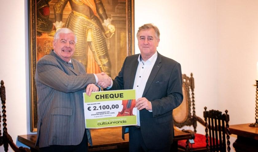 Fons van Pul (rechts) overhandigt Wim Hendriksen een cheque voor Bergh in het Zadel. (foto: Martie Seesing)
