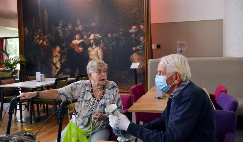 <p>Onder het toeziend oog van De Nachtwacht taxeert de oud-antiquair Jan van &#39;t Riet de geschatte waarde van een van de Delftsblauwe vazen van mevrouw Van den Heuvel. (Foto: Paul van den Dungen)</p>