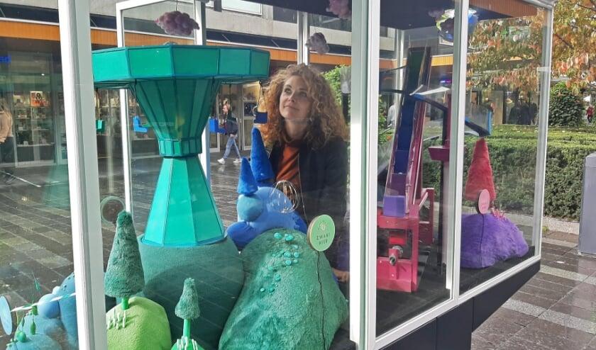 <p>Charlotte van Otterloo in haar &#39;vitrine feestje&#39;. De knikkerlift en draaimolen bewegen wanneer kijkers voor de sensoren bewegen. (Foto: Nynke Vermaat)</p>