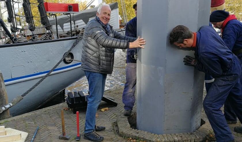<p>Siem van de Marel (links) mag een handje helpen bij het plaatsen van de nieuwe staander in de houder van de stadskraan aan de Westhavenkade. Foto: Peter Spek</p>