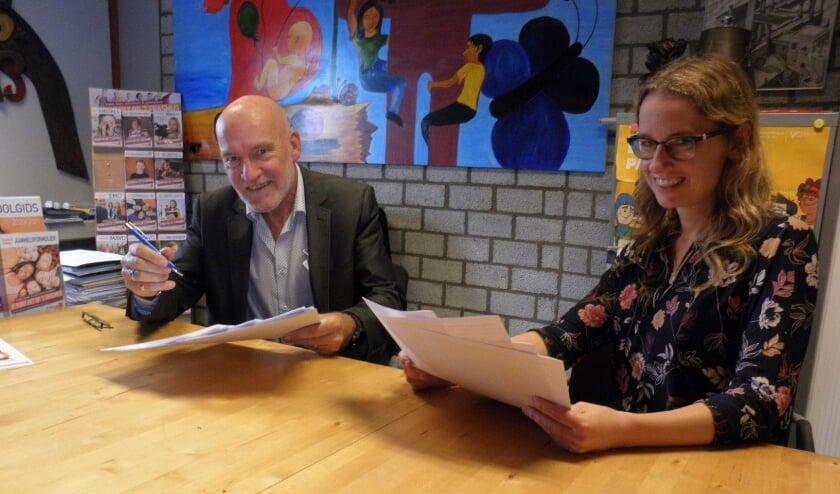 <p>Directeur Jan Brouwer en docente Esther Holstege lezen de verhalen van 120 leerlingen van groep 8. Foto Kees van Rongen</p>