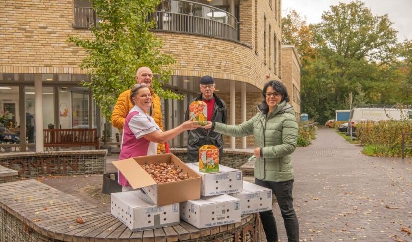 <p>Patty van Vierzen en Wiert Omta overhandigen de tulpenbollen namens Rotary Ermelo aan Ellie en Ton de Kruif van Kroondomein.</p>