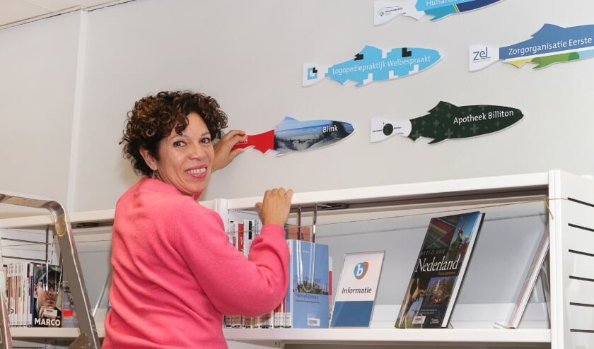 <p>Cinthya de Vaal, oprichter van Blink, in samenwerking en communicatie tijdens het ophangen van de haring met het logo van haar organisatie.</p>