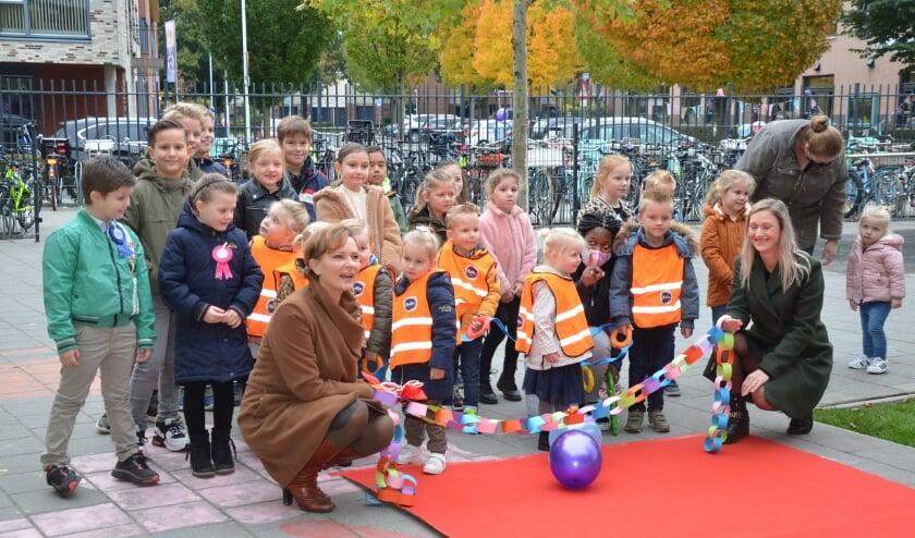 <p>Directeur Pepien Timmermans van kindcentrum Antonius (links) &nbsp;en Lisa van Beerendonk (Partou) met kinderen van elke groep op de rode loper.</p>