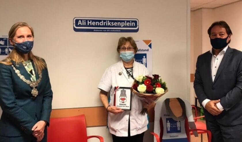 <p>Uit handen van loco-burgemeester Lot van Hooijdonk ontving Hendriksen een 'Zorg goed voor elkaar'-poster. Foto: Diakonessenhuis</p>