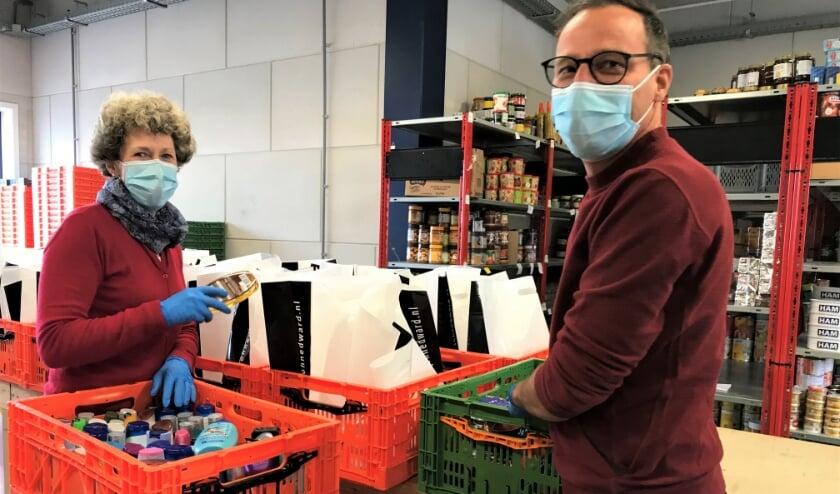 <p>Ren&eacute;e Snoek en Jacco Engelgeer pakken voedselpakketten in. (foto: Frieda Fennell)</p>