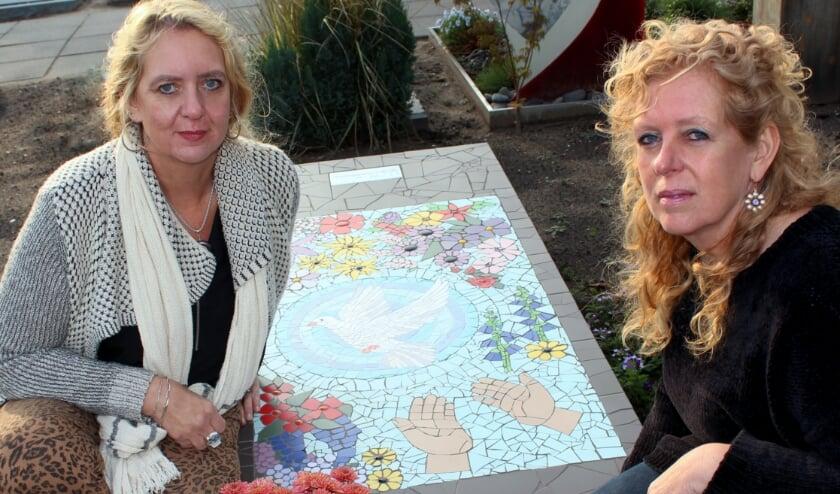 <p>Jolanda (li) en Yvonne eren hun moeder met een zelfgemaakte grafsteen. &#39;Met de bloemen waar ze zo van hield&#39;. FOTO: Morvenna Goudkade</p>