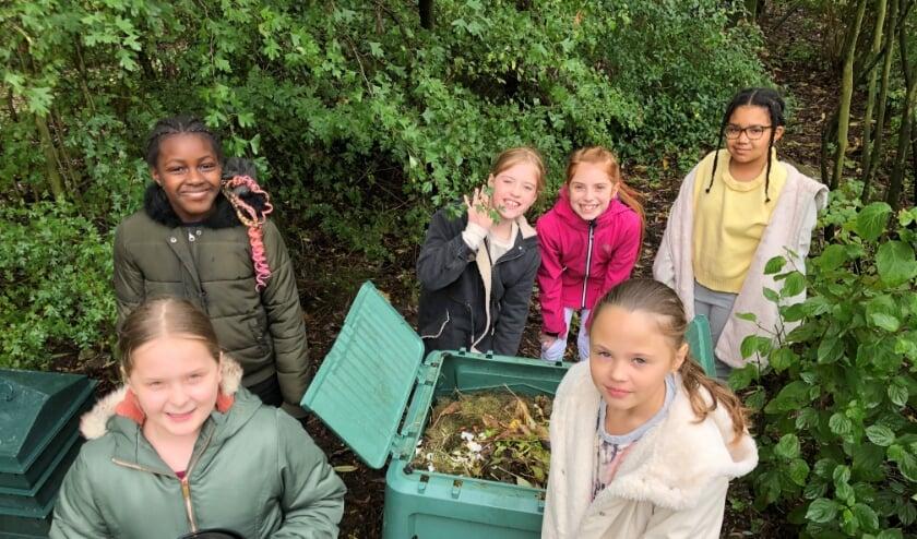 Leerlingen uit groep 6 van de Elisabethschool brengen groenafval naar de composthoop in de lestuin.