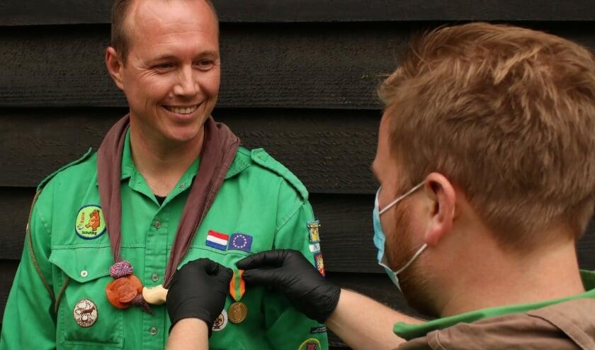 <p>Bram Kroes speldt de medaille op de Scouting blouse van Leon Kuit.</p>