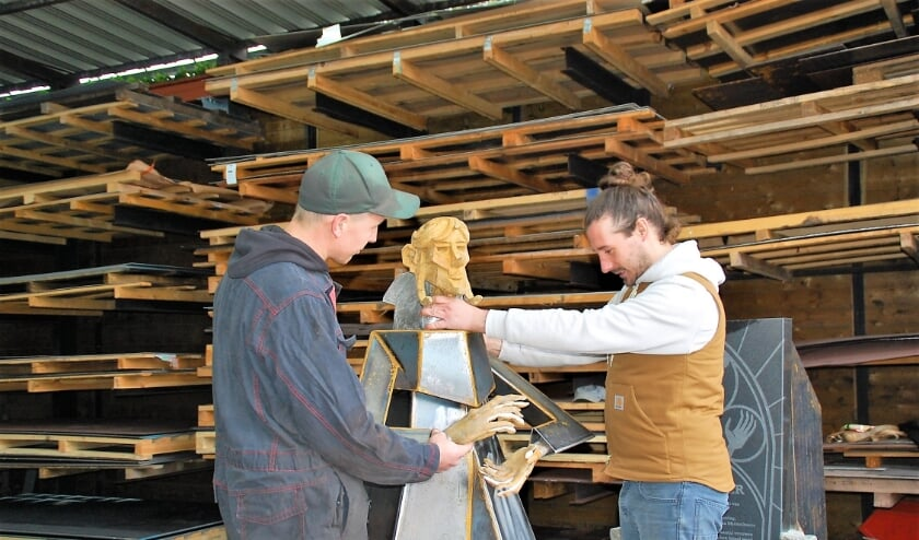 <p>Chris van Hoof en Tom l&#39;Istelle completeren het beeld van de Strijkster. Vrijdag werd het geplaatst nabij de kassen van Jonkers in Middelbeers.</p>