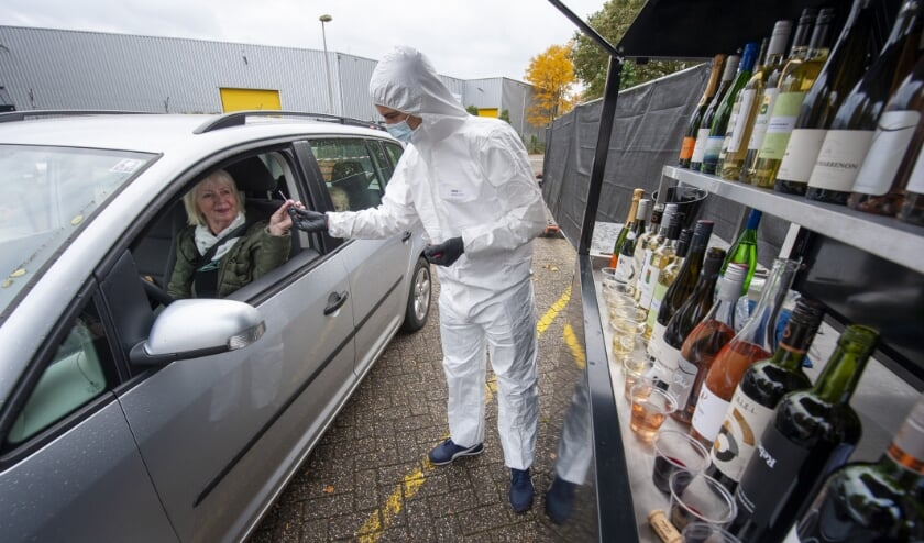<p>Een &#39;wijndokter&#39; laat een bezoeker wijn proeven door middel van een pipetje. (Foto: Robert Hoetink)&nbsp;</p>