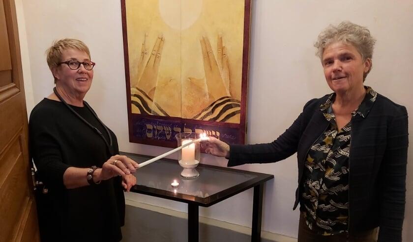 <p>Bea Flierman en Lia Davidse voor het gedachtenisbord. Zaterdag 31 oktober delen zij kaarsjes uit in een kraam bij de Coop in Rossum.</p>