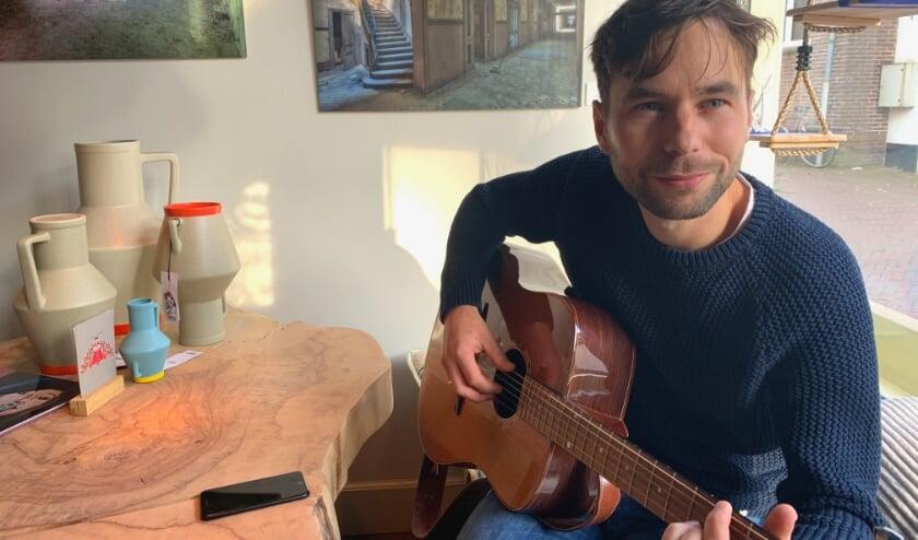 <p>Zichtbaar opgewekt pakt Arend Palland de gitaar met op de klankkast de uitnodigende woorden: &#39;Bespeel mij&#39;.</p>