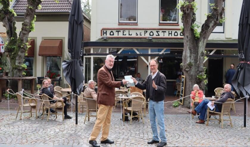 <p>Jan Paasman overhandigt het eerste exemplaar van het wandelboekje aan Jan van de Velde, voorzitter van Ampt Epe.</p>