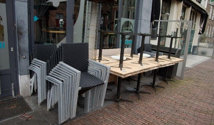 <p>Tafels en stoelen opgestapeld bij een horecazaak. De komende &nbsp;weken is dit het beeld</p>