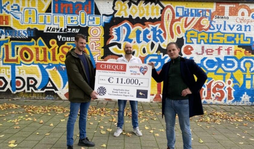 <p><em>Gebroeders Hubert (links) en David (rechts) Van Linschoten bieden Johan Muurlink (midden) een cheque ter waarde van 11.000 euro aan voor zijn stichting Niet Graag een Lege Maag. </em></p>