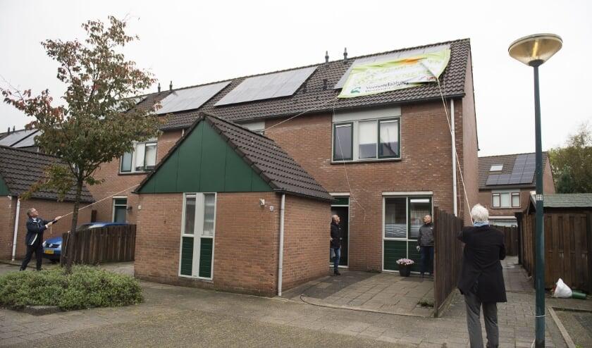 <p>De vlag werd met enioge moeite op het dak bevestigd. Grote afwezige was de zon die middag. (Foto: Veenendaalse Woningstichting)</p>