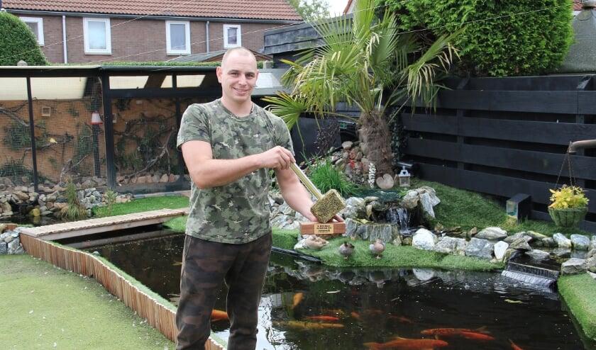 <p>Jurren Engelage in de tuin bij zijn huis in Groessen met in zijn handen Hornbach's Gouden Hamer voor de beste klusser van het land.</p>