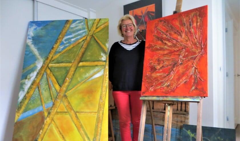 <p>Fineke ten Napel met enkele van haar schilderijen in haar thuisatelier.</p>