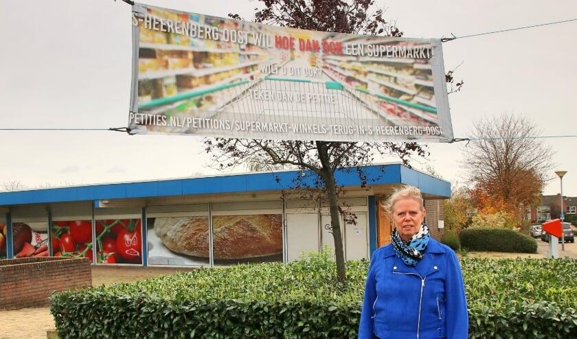 <p>Ina Laarman bij het spandoek dat een oproep doet voor een nieuwe supermarkt in &#39;s-Heerenberg Oost. (foto: Elsie Schoorel)</p>
