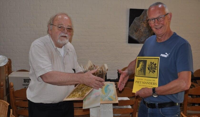 <p>Piet Manders (links) overhandigt de collectie.&nbsp;</p>