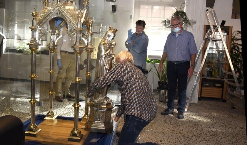 <p>Zilversmid Huub Rogier plaatst het Mariabeeld terug in de ciborium. Foto: Marianka Peters</p>