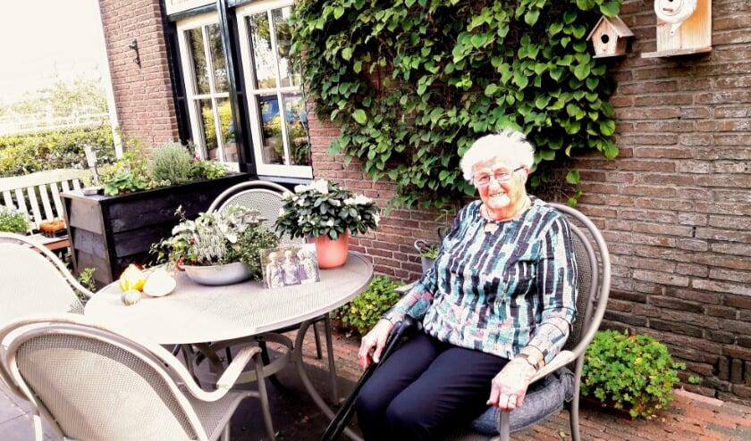<p>Mevrouw Van Manen &ndash; van de Kamp, gaat voor de foto graag even in haar bloementuin zitten. Niet te lang. Het is kouder dan het eruit ziet.</p>