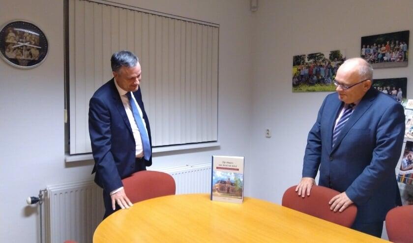 <p>&nbsp;J. Boertje (links) van de Reformatorische Schoolvereniging en burgemeester &nbsp;Hofland bekijken het jubileumboek. (Foto: Reformatorische Schoolvereniging Rijssen)</p>