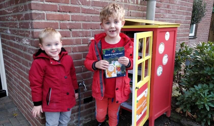 <p>Nathan van 5 en Dani&euml;l van 3 jaar pakken alvast een boek uit de zwerfboekenkast aan de Trekvalk in Veenendaal. (Foto: Esm&eacute;e Schot)</p>