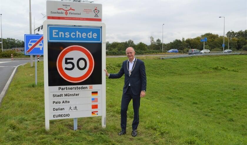 <p>Burgemeester Onno van Veldhuizen bij een plaatsnaambord waar ook partnerstad Stadt Munster is opgenomen. (Foto: PR)</p>