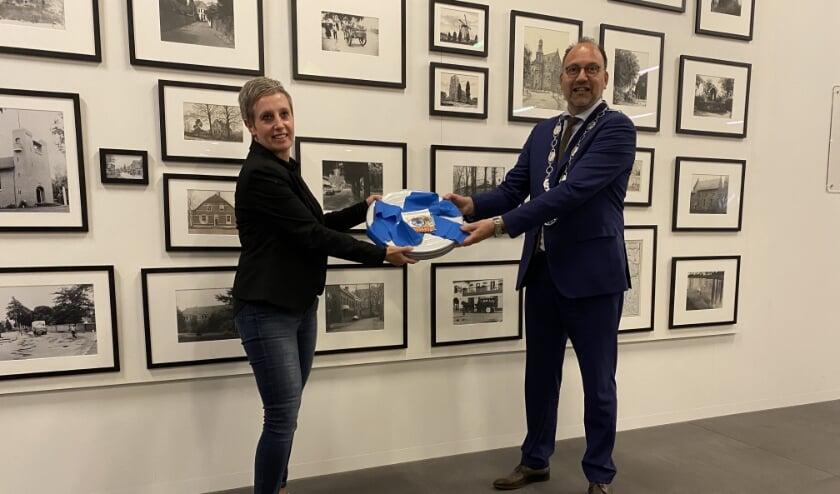 <p>Mari&euml;lle Horsting, voorzitter van Filmhuis Didam, overhandigt 2.600 handtekeningen aan burgemeester Peter de Baat. (foto: Karin van der Velden)</p>