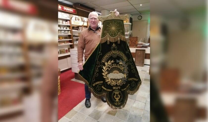 <p>De redactie heeft &nbsp;een verrassing voor Louis meegenomen: een vaandel van het mannenzangkoor Excelsior, een club die door sigarenfabrikant Hillen was opgericht (foto: Indebuurt.nl/delft)</p>