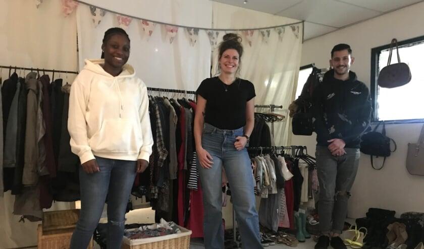 <p>Stagiair Jurenci&euml;ne, jongerencoach Lizzy en vrijwilliger Saad in de MDT Shop</p>