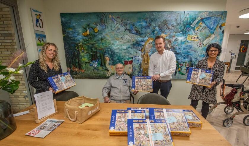 <p>Janneke Bruintjes, meneer Marten Hoeve, Dani&euml;l Brinkman en Patty van Vierzen met de tien legpuzzels in Jan van Haasteren stijl.</p>