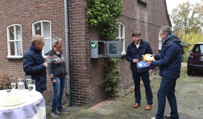 <p>Willy Wartenberg toont de AED aan cardioloog Van der Kraaij. Peter de Leeuw van HartVeilig Den Bosch kijkt toe met bewoonster Marjan Smeulde. Foto: Henk van Esch</p>
