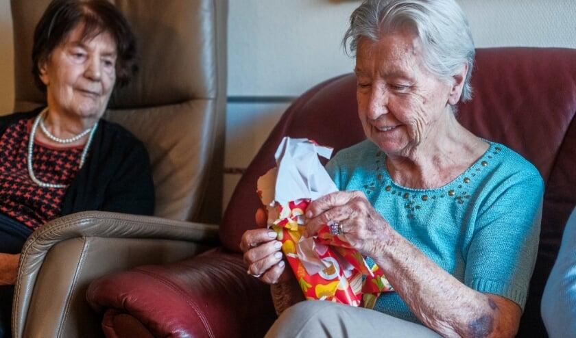 Bewoners van De Roo pakken cadeaus van Sinterklaas uit