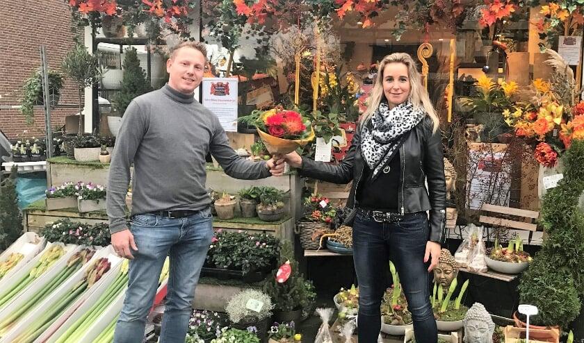<p>Bloemist Ronny van Aggelen verrast mantelzorger Mariska van Brakel met een bloemetje.</p>