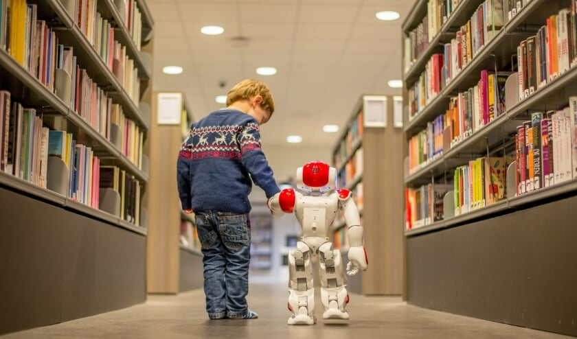 Een jonge bezoeker met biebrobot Bibi.