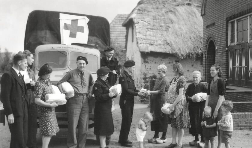 <p>Vanwege de schaarste deelde het Rode Kruis na de bevrijding in &#39;45 voedselpakketten uit, hier aan de Poel in Velddriel. Mevrouw van Gessel neemt het pakket in ontvangst en woonde in de boerderij met de rieten kap.</p>