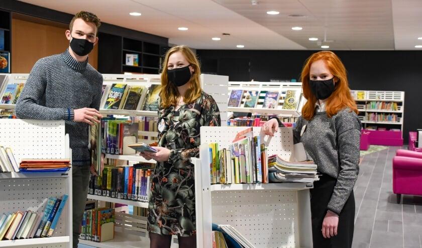 Opruimhulpen Hans-Gerald, Esther-Lydia en Anna-Eline Roestenburg in de bibliotheek van Ermelo