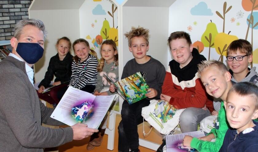 <p>Schrijver Melle van der Poel toont zijn boek aan leerlingen Rune, Feey, Esmee, Jamie, Tyn, Lucas, Sil en Mika. FOTO: Morvenna Goudkade</p>
