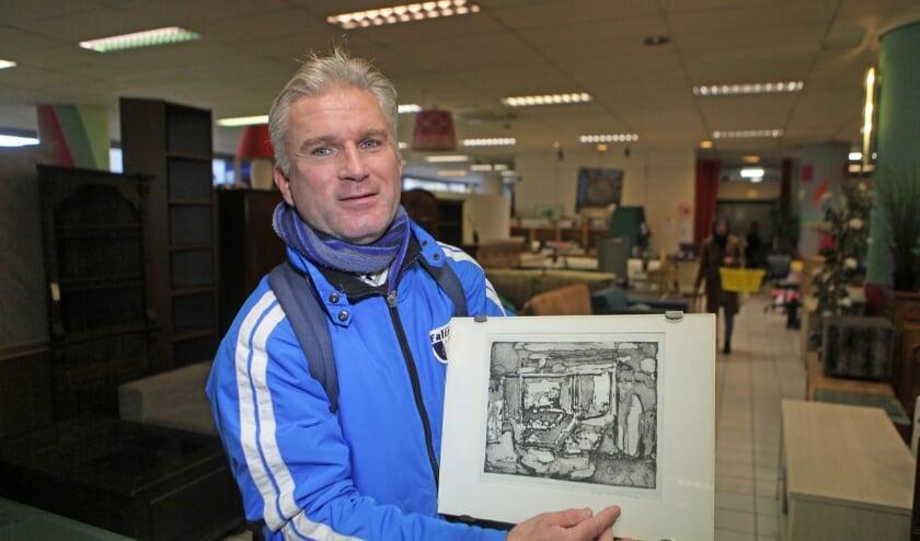 <p>Victor Laurentius in de kringloopwinkel met een ets (Foto: Peter van Zetten).</p>