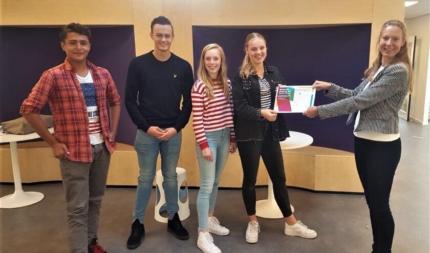 <p>Marjan Duursma van Day for Change overhandigt een leenovereenkomst aan leerlingen van het Titus Brandsma in Velp.</p>