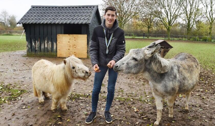 <p>Sem op kinderboerderij Kokiezier met Willie, de 23 jaar oude Shetland pony en Myrna, de 18 jaar oude ezel. (foto: Roel Kleinpenning)</p>