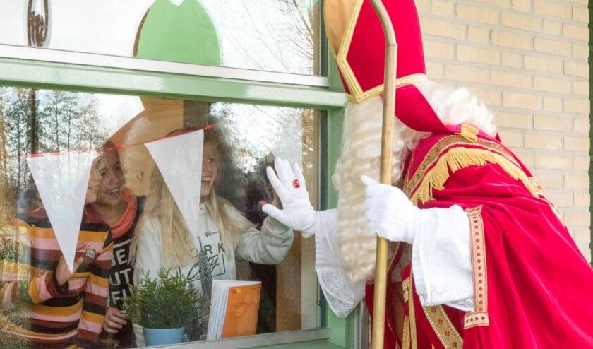 <p>De oudere kinderen op De Bogerd geven Sinterklaas een coronaproof high-five.</p>