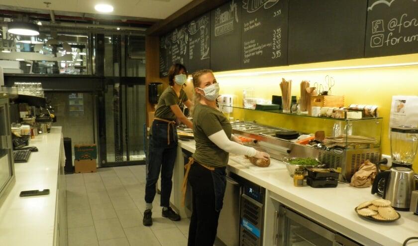 <p>Anita van der Voort op de voorgrond bereidt met een medewerker de lunch in het Forumcafé. Foto Kees van Rongen</p>