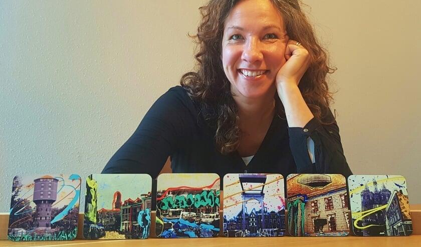 <p>Marieke Brouwers met een set van zes Zwolse onderzetters. Door het wegvallen van workshops en teambuildingsbijeenkomsten hield ze tijd over en maakte de onderzetters.</p>