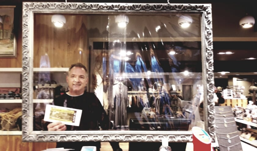 <p>Rob van Wonderen, voorzitter van de Bennekomse Ondernemers, poseert achter zijn fraai ingelijste anticorona-baliescherm, met een Cadeaubon.</p>